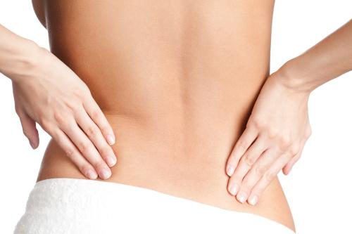 Femme qui se touche le dos aux endroits où pratiquer le lifting du dos