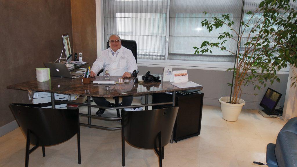 photo du Docteur Gilbert VITALE dans le bureau de sa clinique de chirurgie esthétique à Lyon